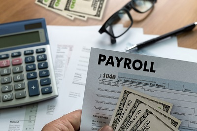 close up of paper that says payroll with cash and calculator